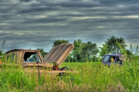 Old wrecked vehicles abandoned in field done in HDR Stock Photo