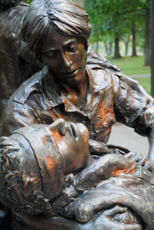 Bronze statue of female nurse caring for wounded solider near the Vietnam Memorial on the National Mall in Washington, DC.