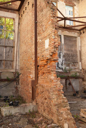 Partially collapsed masonry wall shown on interior of ruined building.