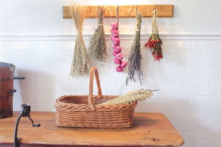 Fresh herbs and garlic drying on the wall of a beautiful kitchen.