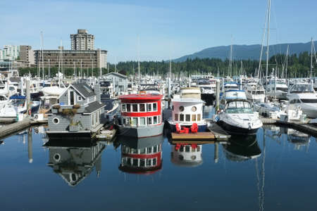 Vancouver, Canada - June 15, 2015: View of marina in downtown Vancouvern with houseboats and sailboats docked on summer morning.