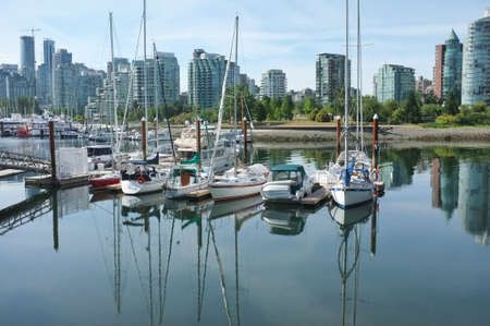 placid water: Vancouver, Canada - June 15, 2015: Boats docked at a marina in Vancouver, Canada, with tall buildings in the background. Editorial