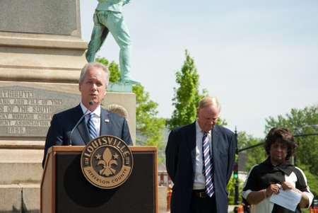 Louisville, KY - April 29, 2016: Mayor Greg Fischer annouces plans to remove a Confederate monument from South Third Street, near the University of Louisville campus. University president James Ramsey and another offical stand behind the mayor. Editöryel