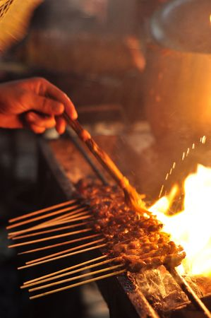 borneo: Cook is putting sauce on some satay with a reed brush.