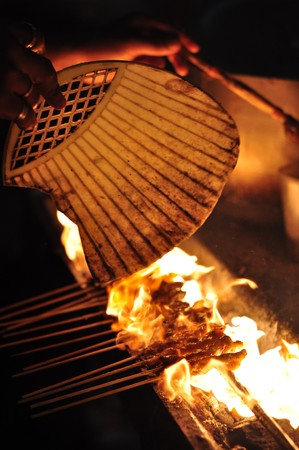 fanned: Photo taken in Sabah, Malaysia. Satay on a grill being fanned to fire-up the charcoal.