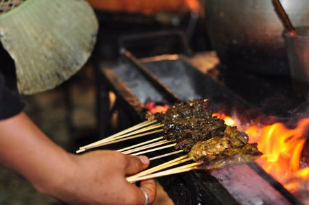Satay cooked on grill. Traditional food of southeast asia.