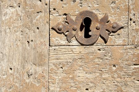 Keyhole on an old wooden door. photo