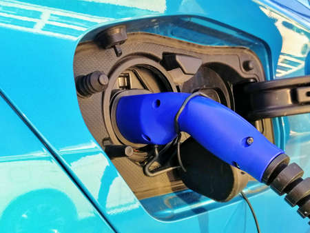 An electric powered car is being charged. Photo shows the charger inserted into the vehicles charging point behind the fuel filler cap