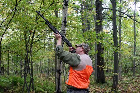 hunter shooting shotgun in a forest background