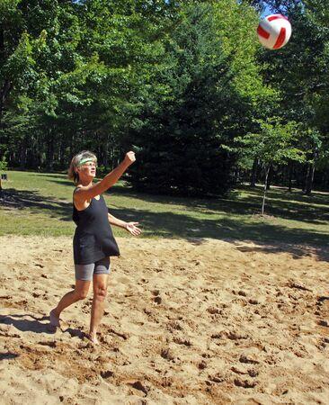 pelota de voley: una mujer sirve para juego de pelota de voley playa Foto de archivo