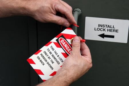 電気機器の危険タグをロックを置く男