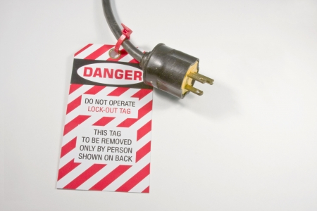 electrical lock out tag on an extesion cord over white Stock Photo