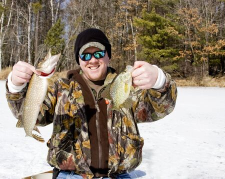 ice fisherman holding a northern pike and a crappie caught on the lake
