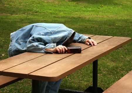 man assleep on a picinic table with beer bottle in hand Stock Photo