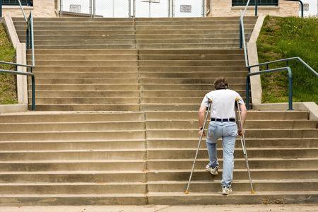 목발에있는 남자가 큰 계단을 오르다.