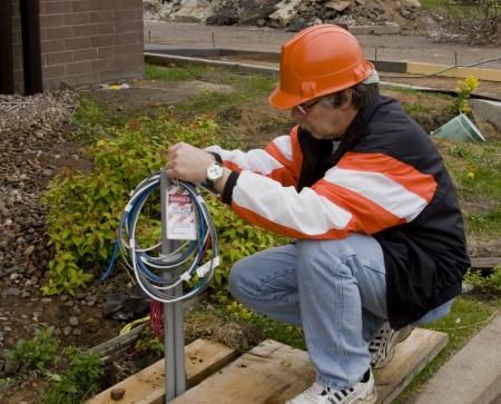 electricista de construcci�n poniendo un peligro de bloqueo de etiquetas en las conexiones de cable Foto de archivo
