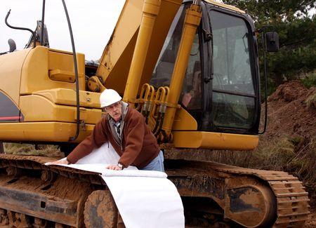 Contratista de casco blanco, con los planos delante de equipo pesado
