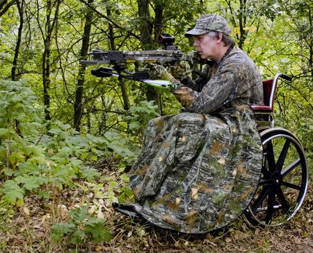 crossbow: handicapped hunter in a wheelchair with a crossbow in the woods Stock Photo