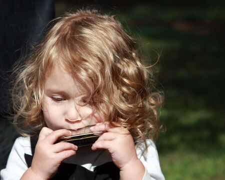 little blonde girl playing a harmonica outdoors