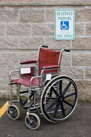 Rol stoel is geparkeerd in een gehandicapt parkeren kraam Stockfoto - 5665739