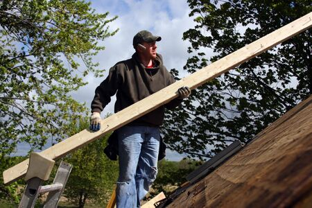 carpenter standing on roof with a board in hands