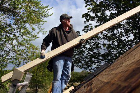 Timmer man staande op het dak met een bord in handen