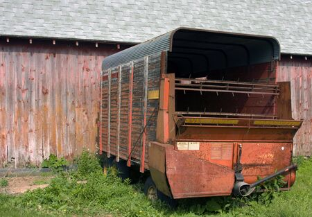 crimper: old farmers chopper wagon with a red barn in the background