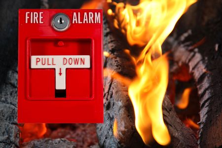 fire alarm pull station with fire as the background Stock Photo