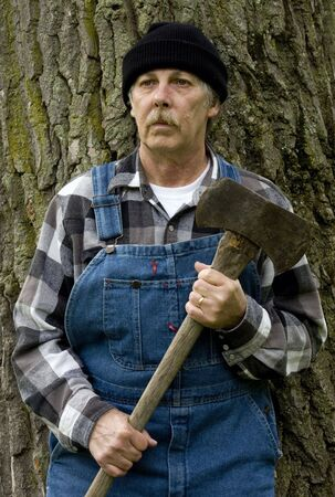 portrait of a lumberjack logger with axe in hand in vertical format