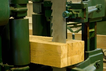 idustrial band saw cutting a log into boards