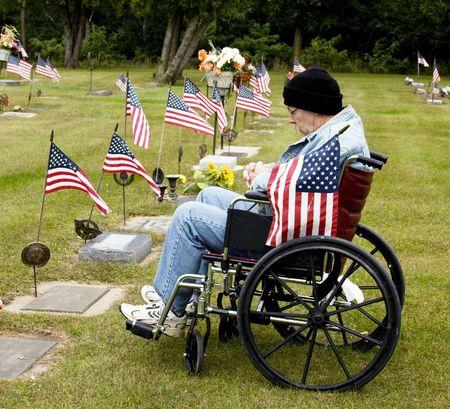desactivado el veterinario de la guerra en una silla de ruedas sosteniendo la bandera americana en una tumba