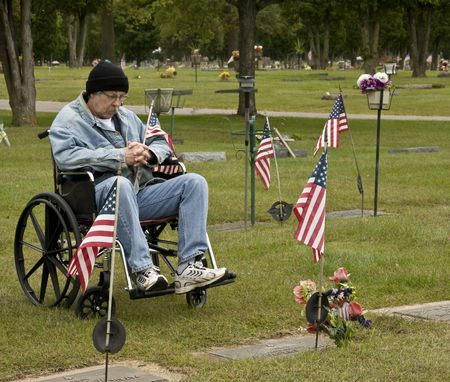 disabled american veteran at a grave holding an American flag