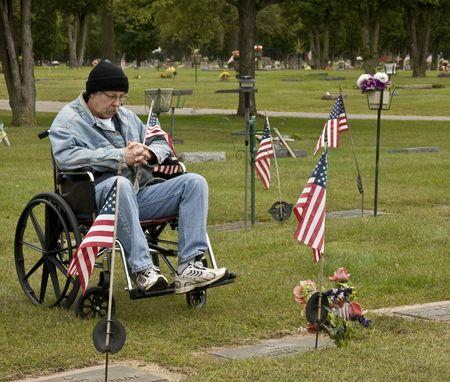 met een handicap Amerikaanse veteraan bij een graf met een Amerikaanse vlag  Stockfoto