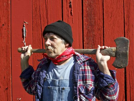 lumberjack portrait in front of a barn with an ax on his shoulders Zdjęcie Seryjne