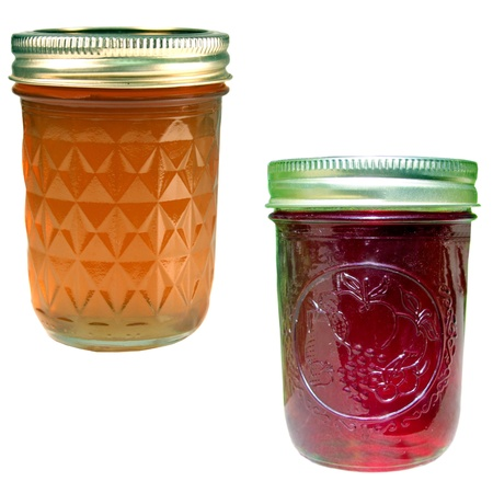 canned fruit:  apple jelly and strawberry jam jars isolated over a white background