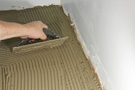 preperation: construction worker trowling a floor with mortar for tile preperation