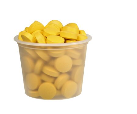 medicine cup full of yellow pills isolated over white background