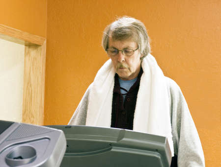 man doing exercise on a treadmill with a towel on his shoulders