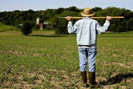 boer staande in een veld met een schoffel op zijn schouders met bomen op de achtergrond