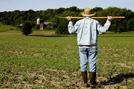 hoe: farmer standing in a field with a hoe on his shoulders with trees in the background