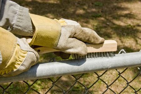 werknemer met handschoenen aan staalborstel een hek