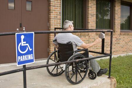 gehandicapte man in een rolstoel te duwen een gehandicapte ingang knop Stockfoto