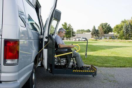 silla de ruedas: conversión de discapacidad levantar van con un hombre en silla de ruedas en la puerta