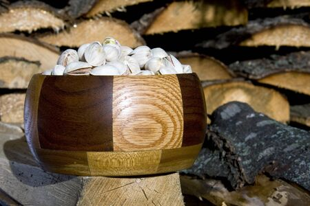 bowl of pistachio nuts against a wood pile backgrounf