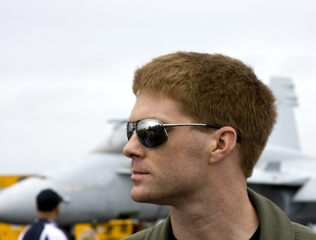 aviator: u.s. navy pilot profile with a jet in the background Stock Photo