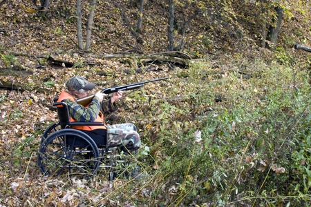 disabled hunter in a wheelchair with a woods in the background photo