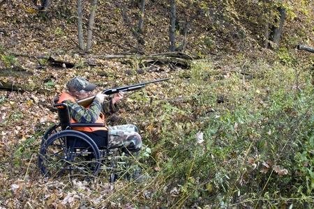 uitgeschakeld jager in een rolstoel met een bos op de achtergrond