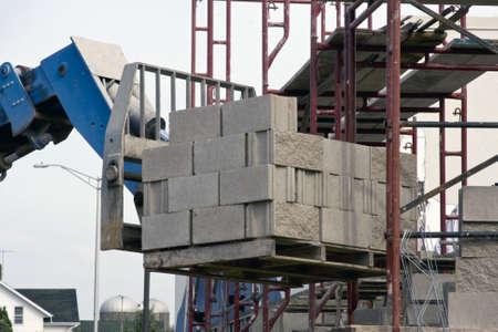 fork lift: carga de ladrillos que se levant� por un ascensor tenedor a un scafold Editorial