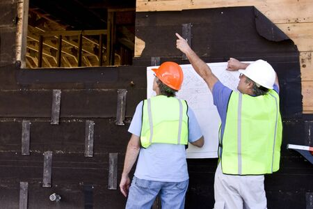 two architect contractors looking at blueprints against a building being built Imagens