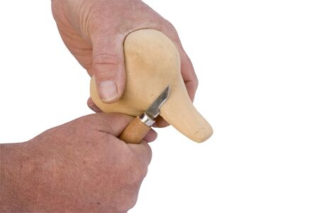 whittle: wood carver shaping a ducks head with a knife isolated over a white background with a clipping path at original size